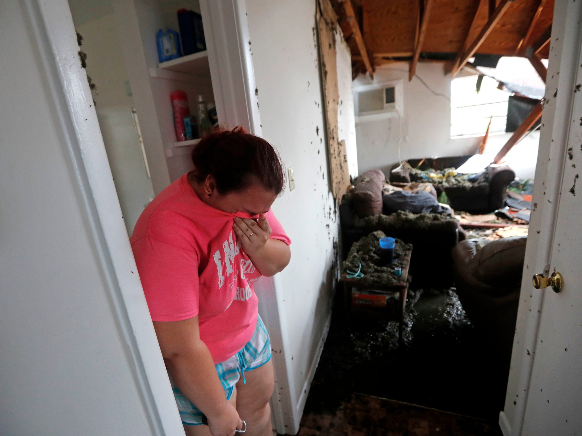 Kaylee O'Brian weeps inside her home after several trees fell on it during Hurricane Michael in Panama City, Fla.