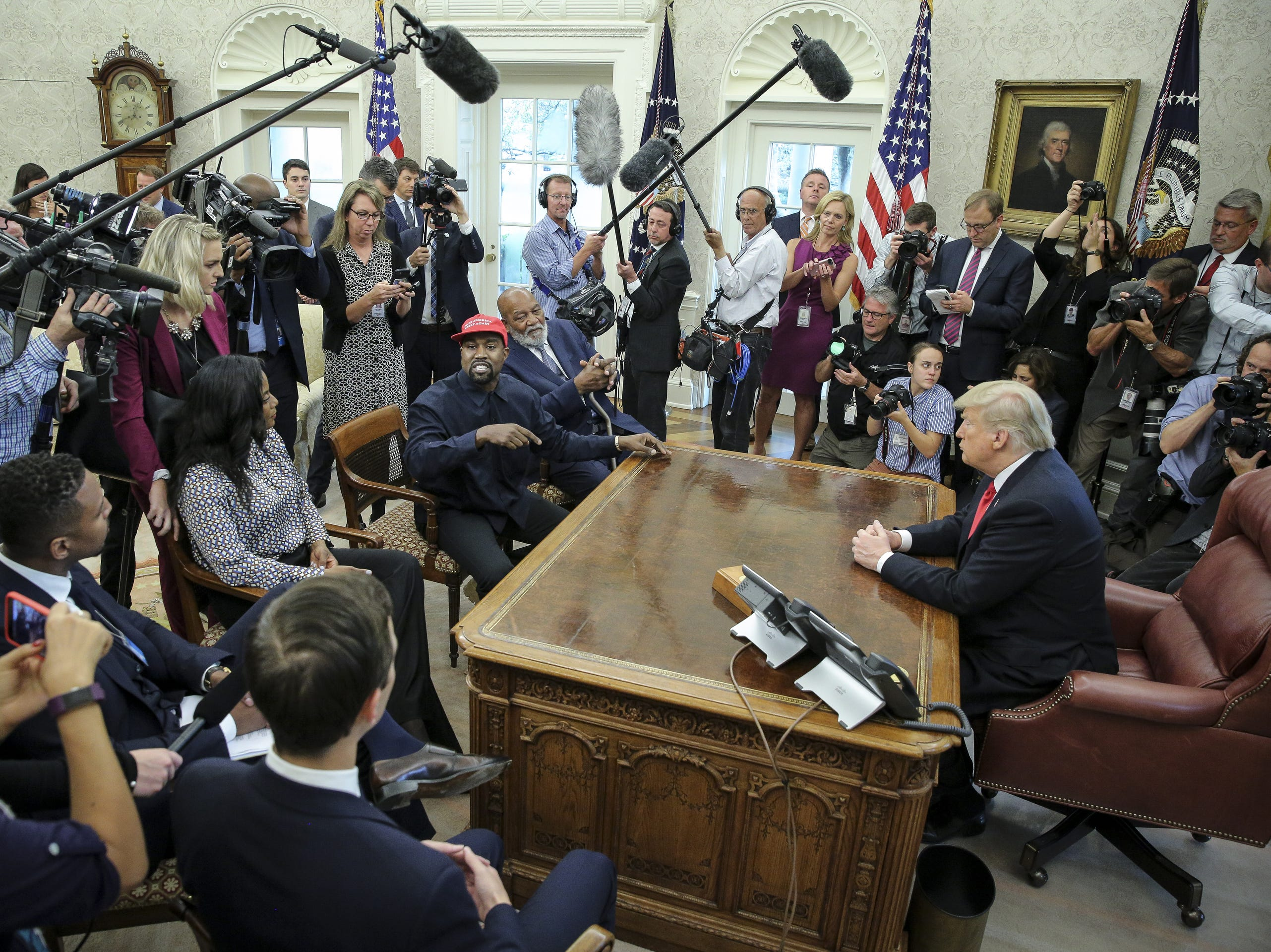 Rapper Kanye West, center, speaks during a meeting with President Donald Trump in the Oval office of the White House.  Former football great Jim Brown sits to the left of West.