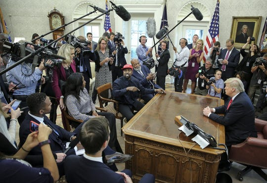 Rapper Kanye West, center, speaks during a meeting with President Donald Trump in the Oval office of the White House. The former soccer player Jim Brown is to the left of West.