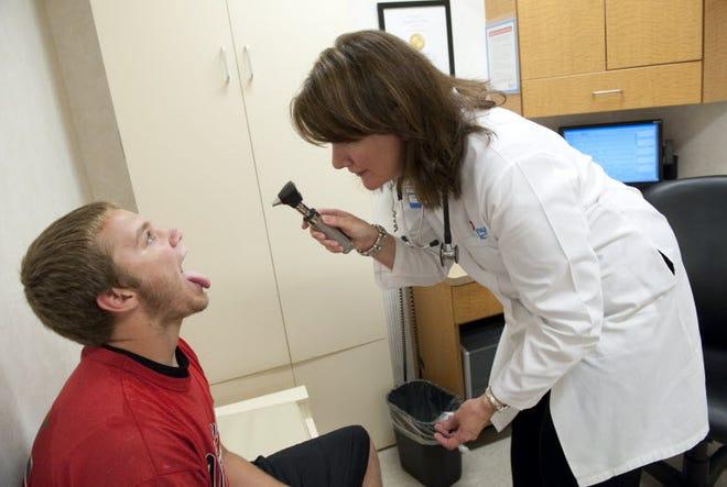 Nurse practitioner Anne Pohnert checking Ryan Farley, July 28, 2011, Vienna, Va.