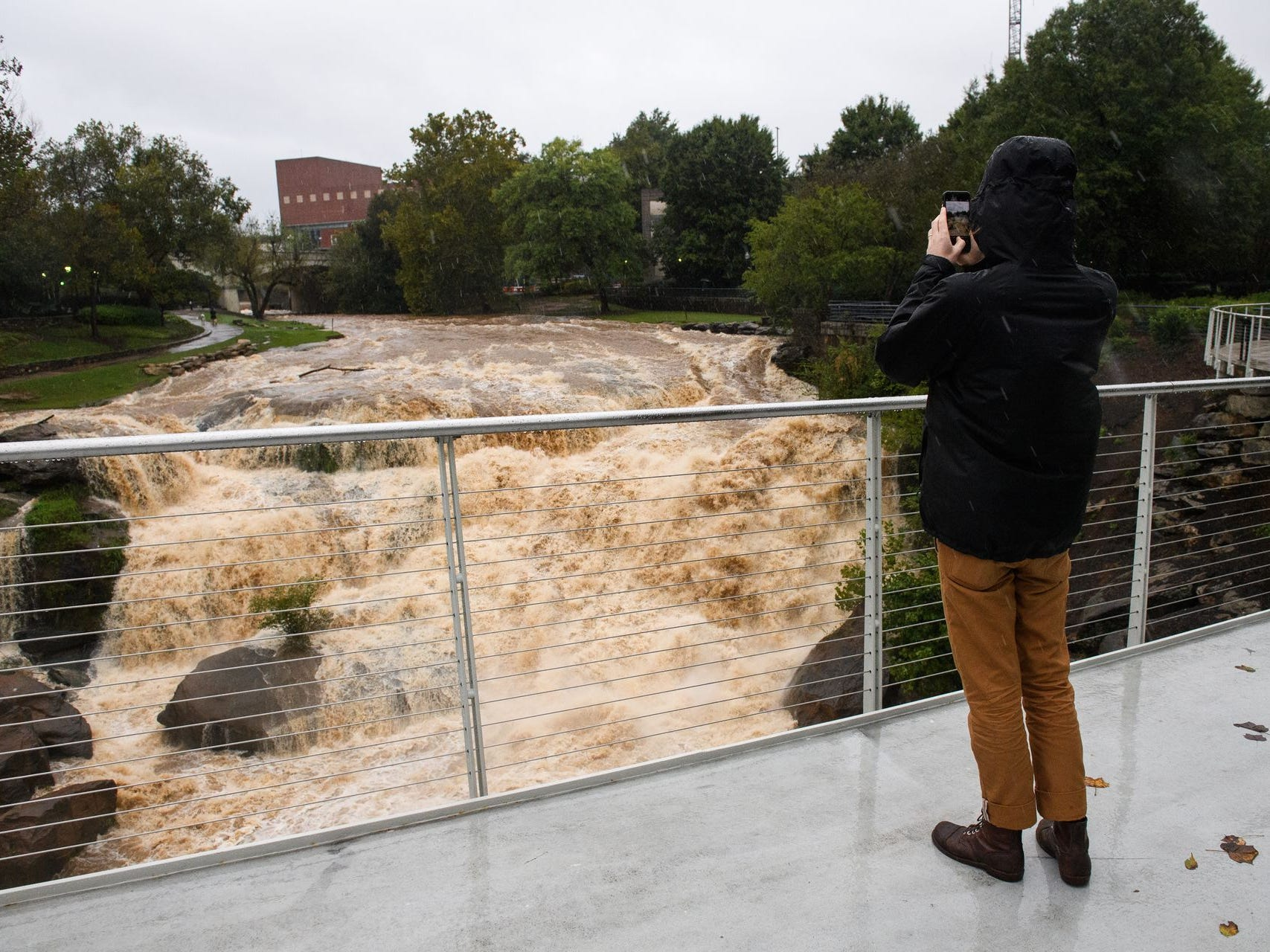 Asher McDougall takes a photo of an elevated Reedy River as Tropical Storm Michael hits the Greenville, S.C. area on Thursday, Oct. 11, 2018.