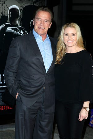 "Arnold Schwarzenegger, seen here in July 2018 with Heather Milligan, says he regrets ""stepping over the line with women"" over the years."