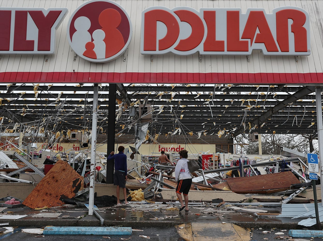 PANAMA CITY, FL - OCTOBER 10:  People look on at a damaged store after Hurricane Michael passed through on October 10, 2018 in Panama City, Florida. Michael made landfall at Mexico Beach today a Category 4 storm, with maximum sustained winds of 155 mph, the most powerful storm ever to hit the Florida Panhandle.  (Photo by Mark Wallheiser/Getty Images) ORG XMIT: 775240672 ORIG FILE ID: 1051849594