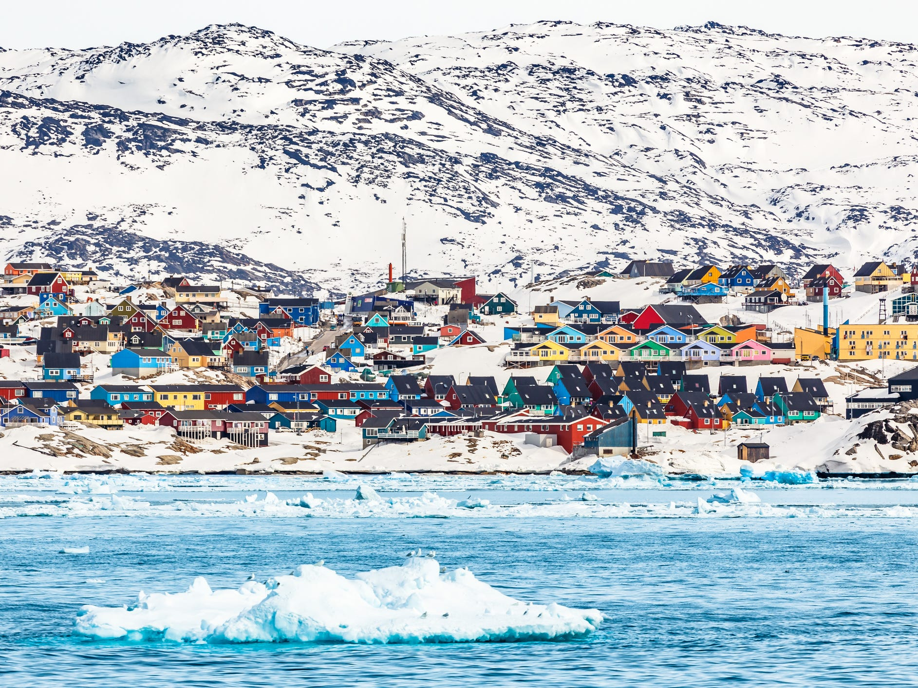 Ilulissat, Greenland: Set against the subdued color palette of the Arctic — white ice, gray rocks, brown tundra grasses — Ilulissat's vividly painted houses bring a spot of cheer to this remote outpost.