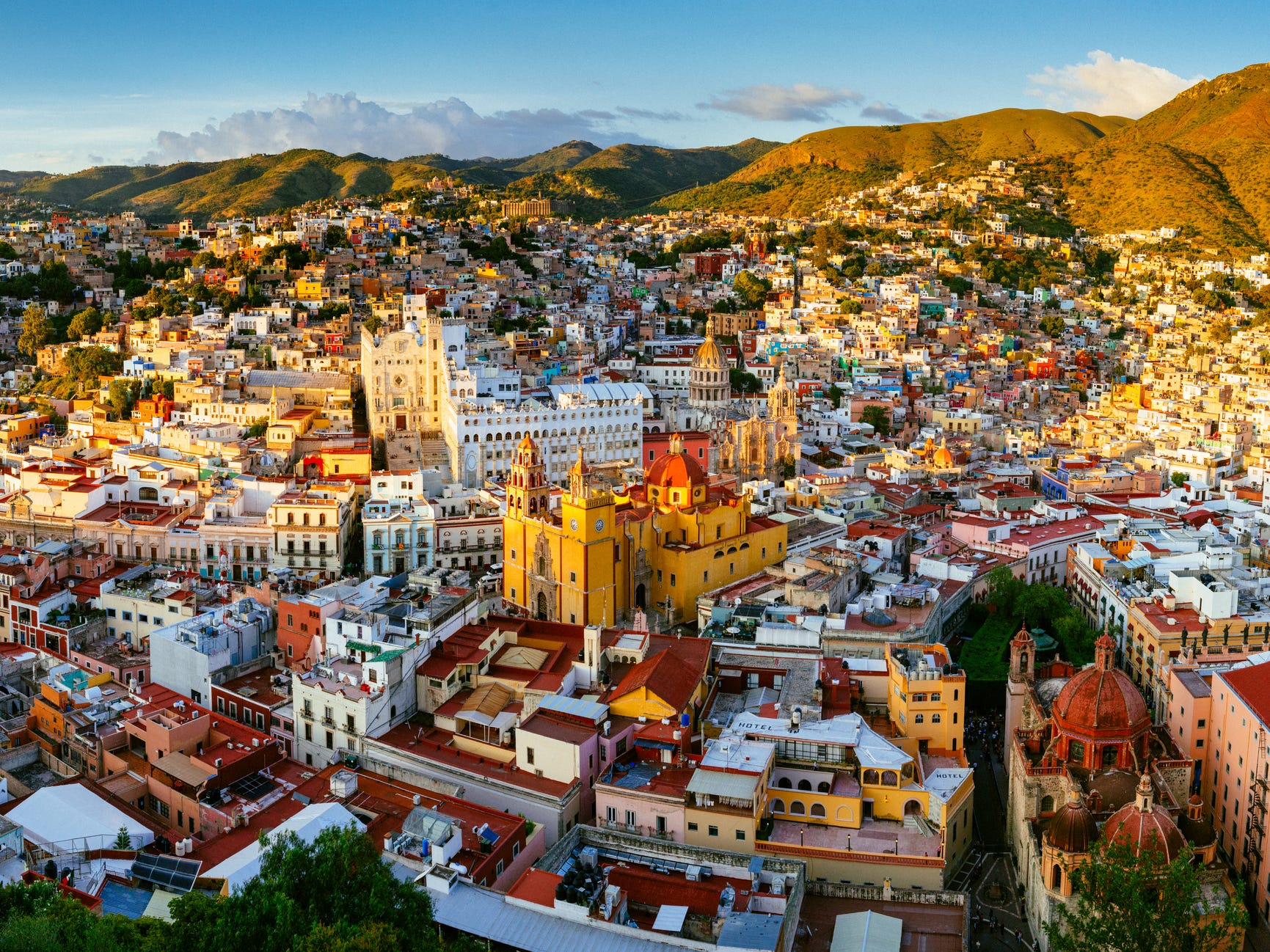 The hills around the city center are blanketed with houses in every shade, while the historic center features cobblestone streets and a striking basilica painted in bright yellow and red.