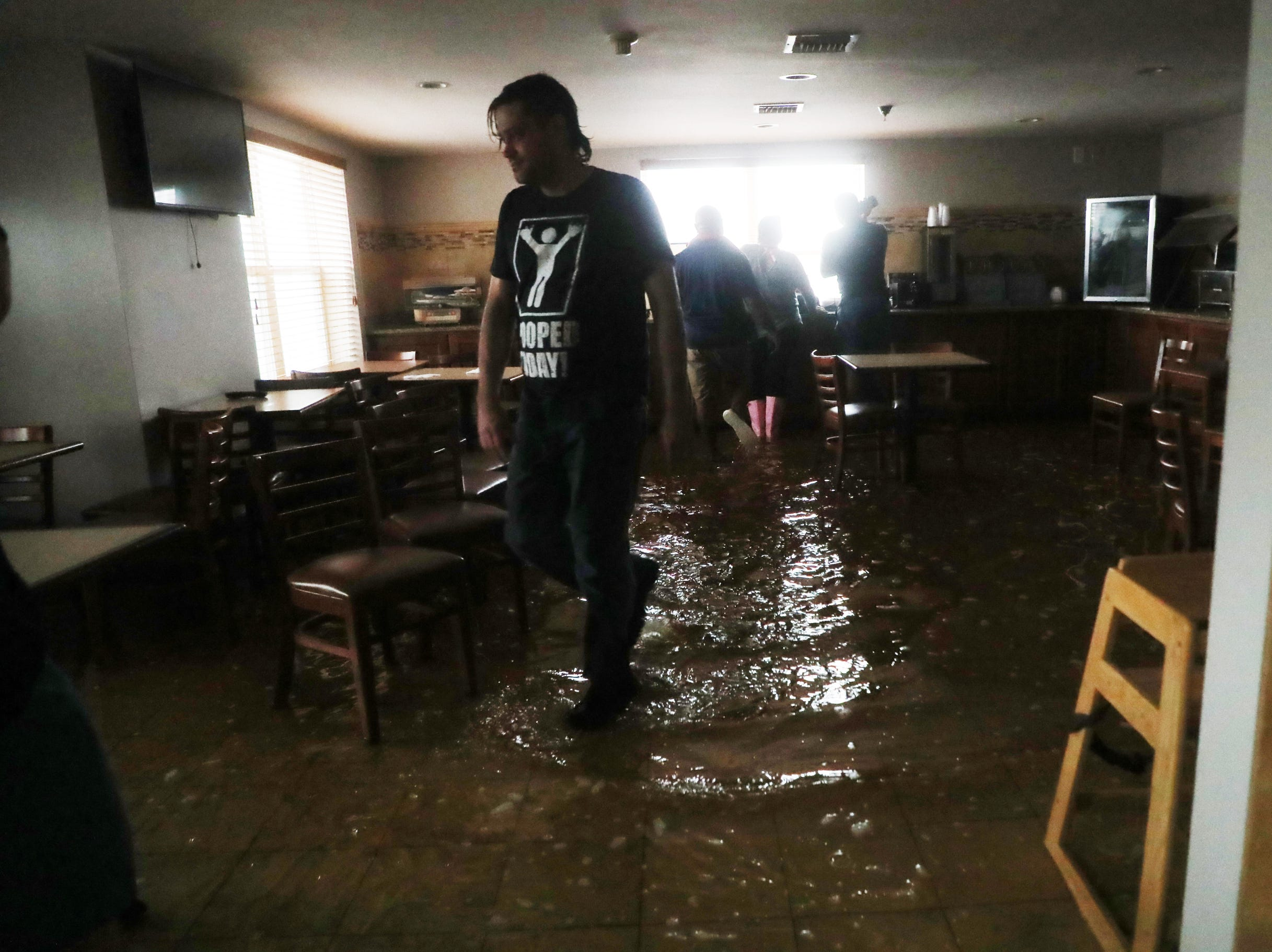 Jacob Merritt walks through a flooded hotel cafeteria at the Country Inn in Panama City, Fla.