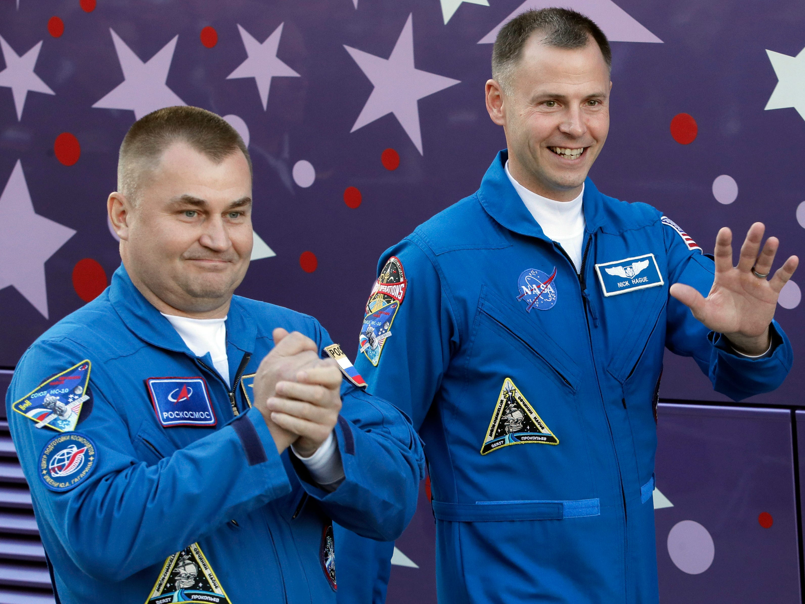 CORRECTS POSITION OF ASTRONAUT - U.S. astronaut Nick Hague, right, and Russian cosmonaut Alexey Ovchinin, members of the main crew to the International Space Station (ISS), wave to their relatives walking to a bus prior to the launch of Soyuz-FG rocket at the Russian leased Baikonur cosmodrome, Kazakhstan, Thursday, Oct. 11, 2018. (AP Photo/Dmitri Lovetsky) ORG XMIT: XDL104