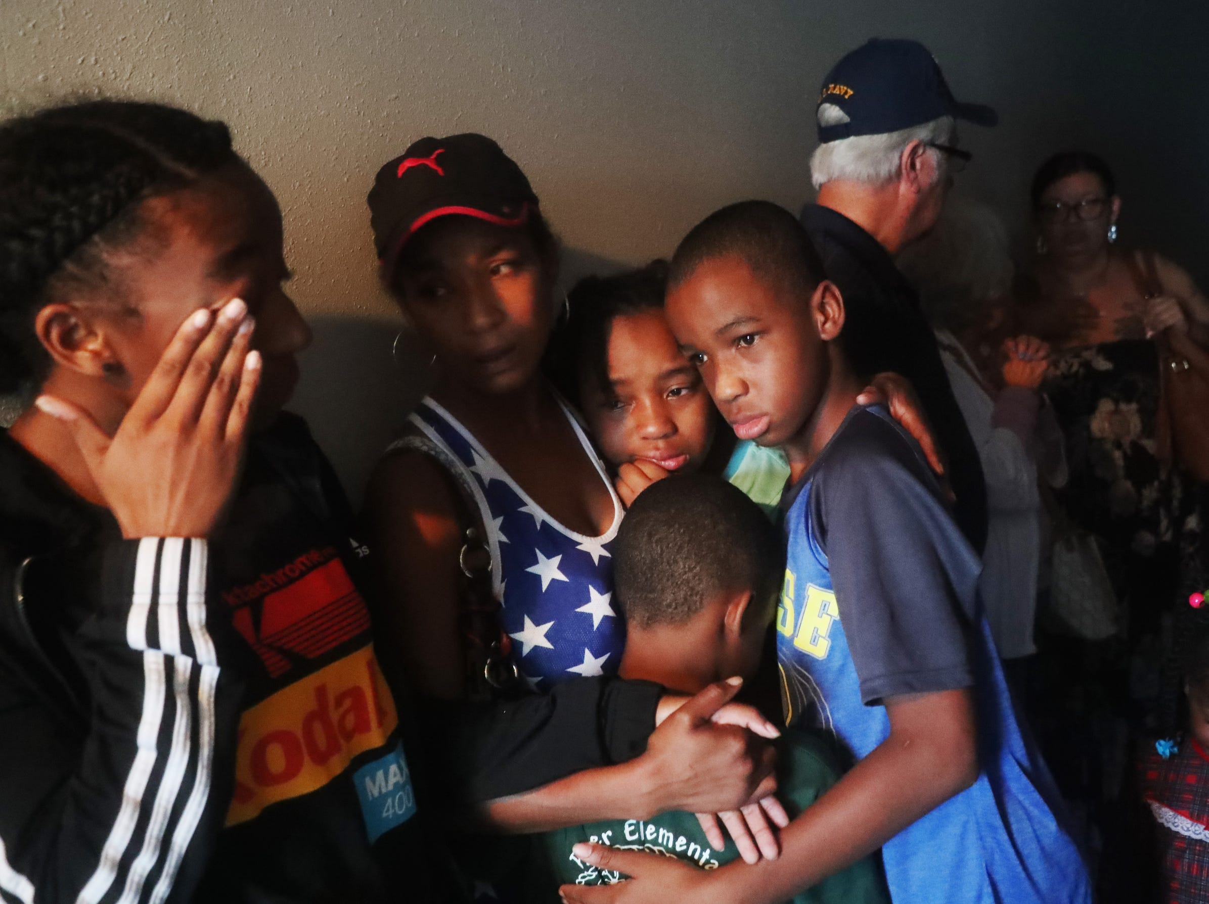 Shekinah Waddell, 2nd left, hugs her children prays with her children, Trinity, Christian and Caris Devore, at the Country Inn in Panama City, Fla., as the height of Hurricane Michael passes through, on Wednesday.