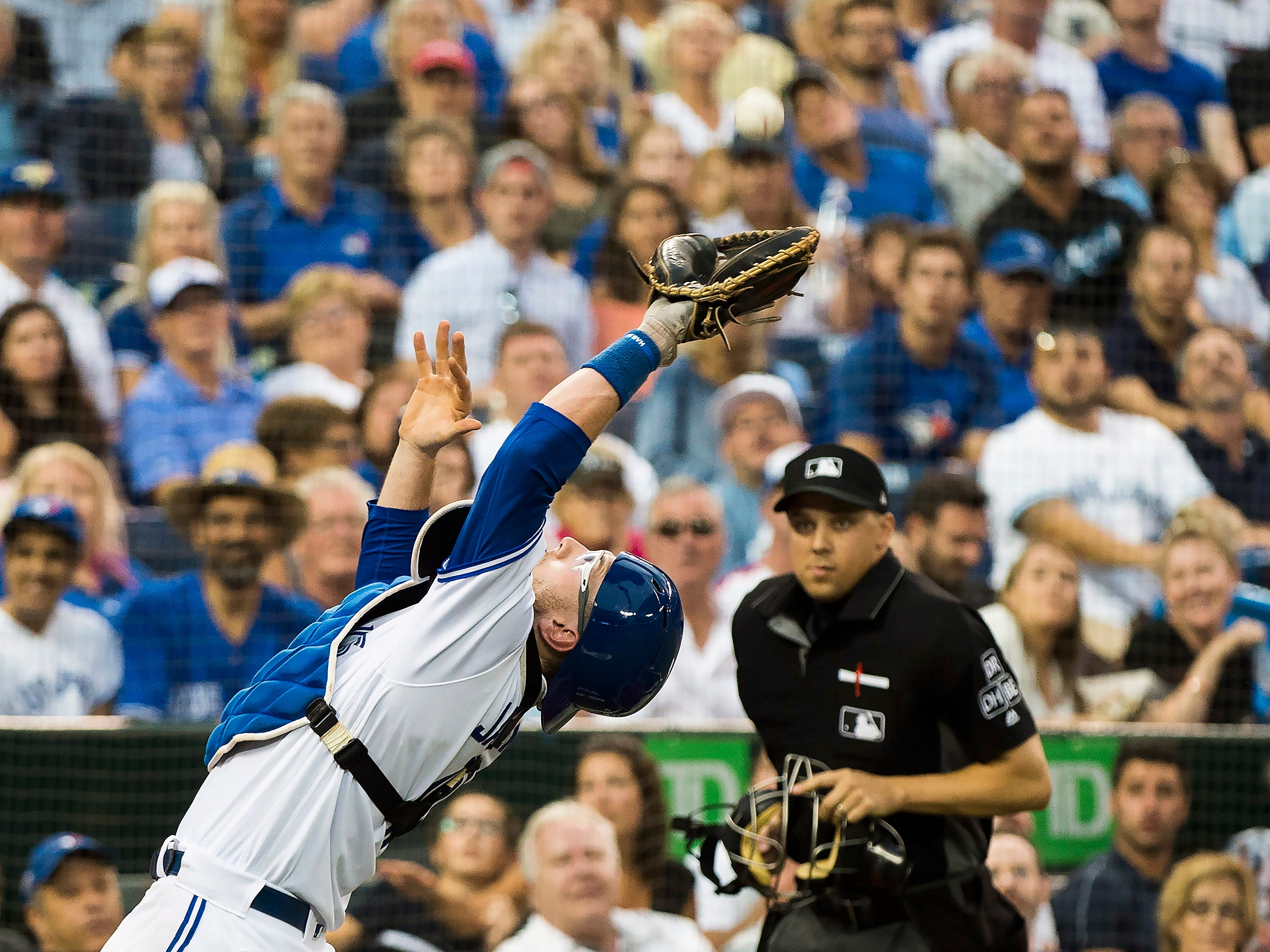 Toronto Blue Jays catcher Danny Jansen (9) makes a pop up catch behind home plate to out Baltimore Orioles third baseman Renato Nunez (39) during third inning baseball action in Toronto on Monday, Aug. 20, 2018. (Nathan Denette/The Canadian Press via AP)