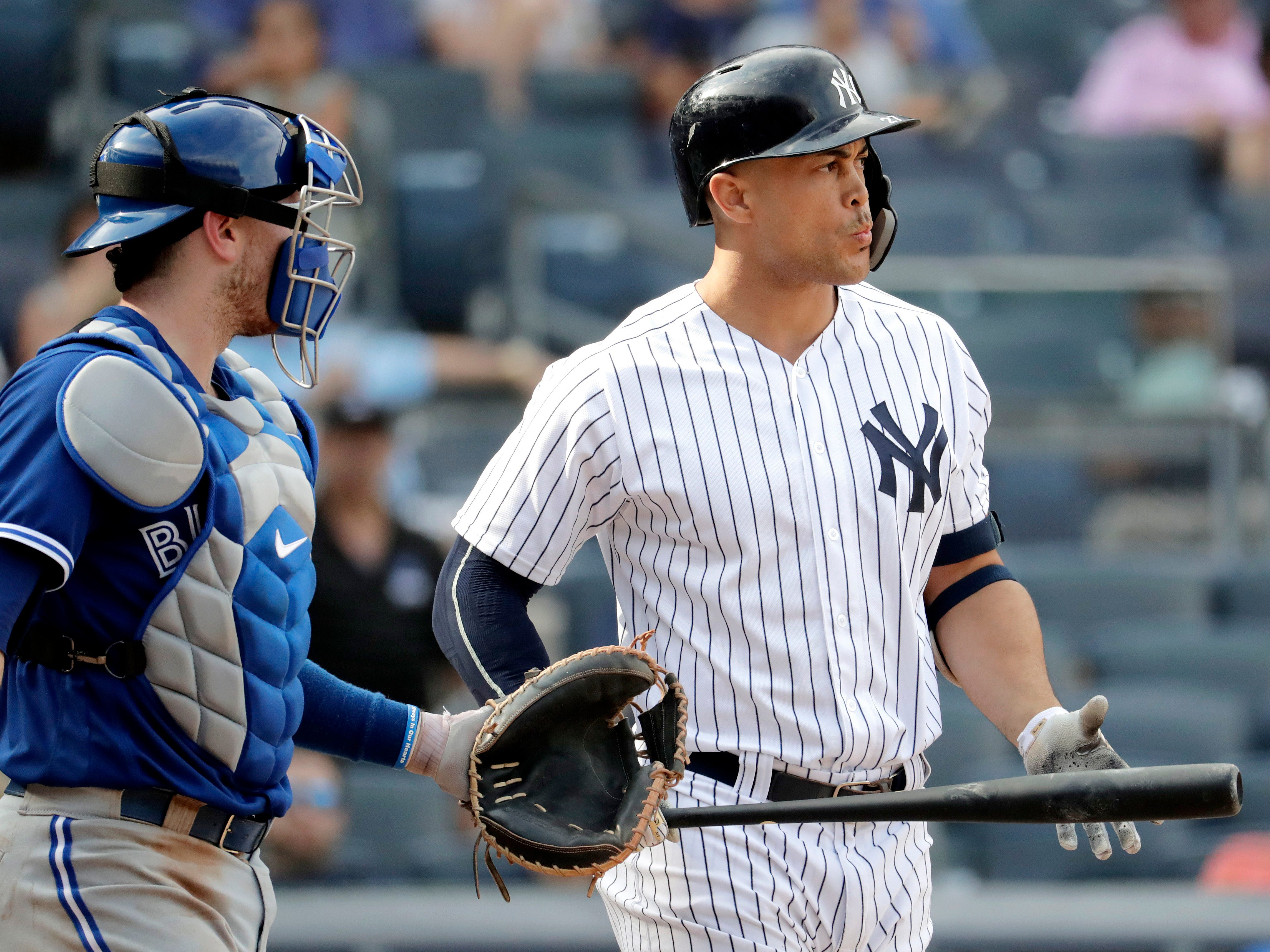New York Yankees designated hitter Giancarlo Stanton, right, looks toward the mound as Toronto Blue Jays catcher Danny Jansen watches him after Stanton was hit by a pitch from relief pitcher Luis Santos during the eighth inning of a baseball game, Saturday, Aug. 18, 2018, in New York. (AP Photo/Julio Cortez)