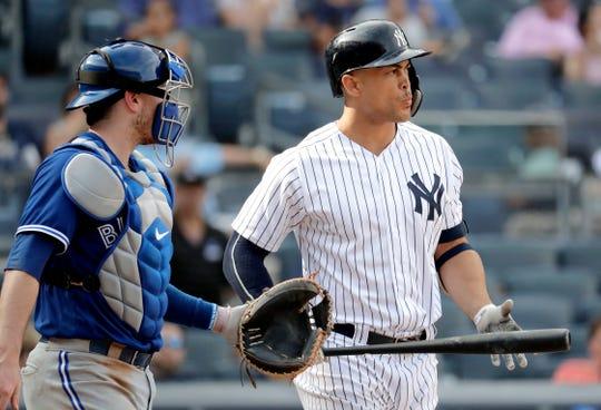 Danny Jansen glances at New York Yankees slugger Giancarlo Stanton during a game at Yankee Stadium.