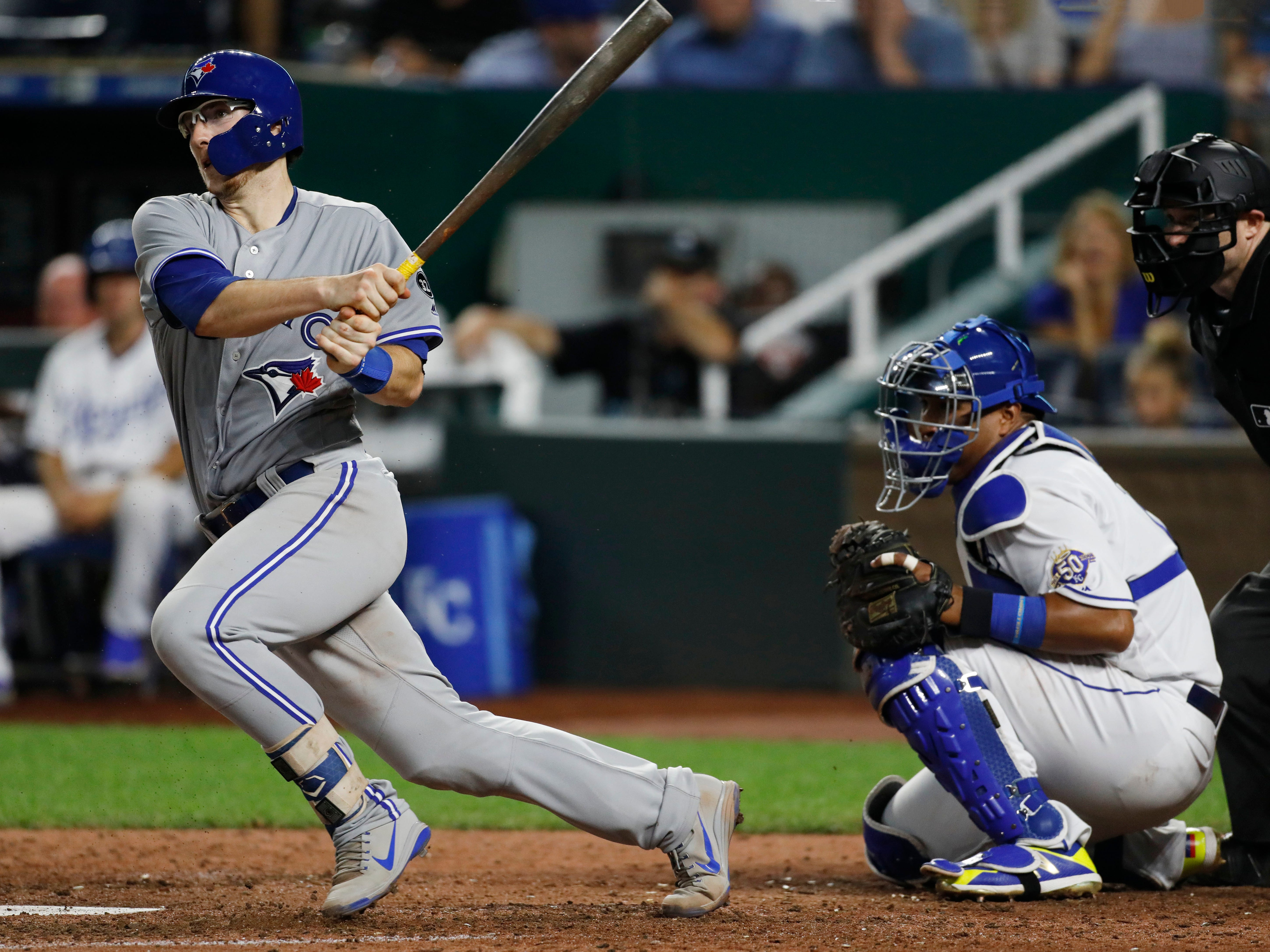 Toronto Blue Jays' Danny Jansen, left, hits a single in his first major league start as Kansas City Royals catcher Salvador Perez, right, looks on in the eighth inning of a baseball game at Kauffman Stadium in Kansas City, Mo., Monday, Aug. 13, 2018. The Royals defeated the Blue Jays 3-1. (AP Photo/Colin E. Braley)