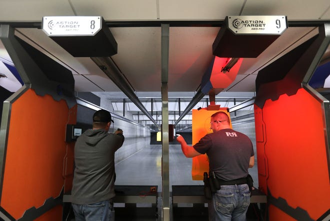 Jake Steinbrink, left, of Hilbert fires his gun as Ben Bastian of Brillion programs his target distance in the shooting range at Trigger Action Sports.