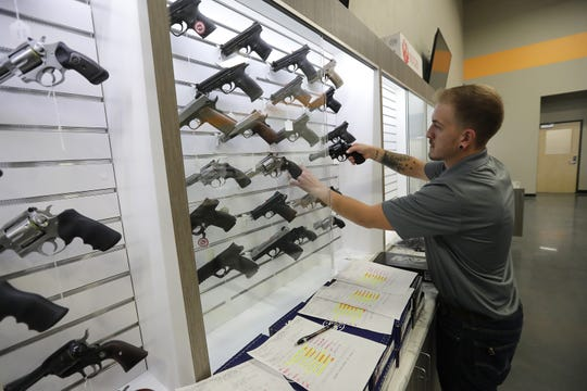 Employee Justin Brownson puts guns on display at Trigger Action Sports in Little Chute.