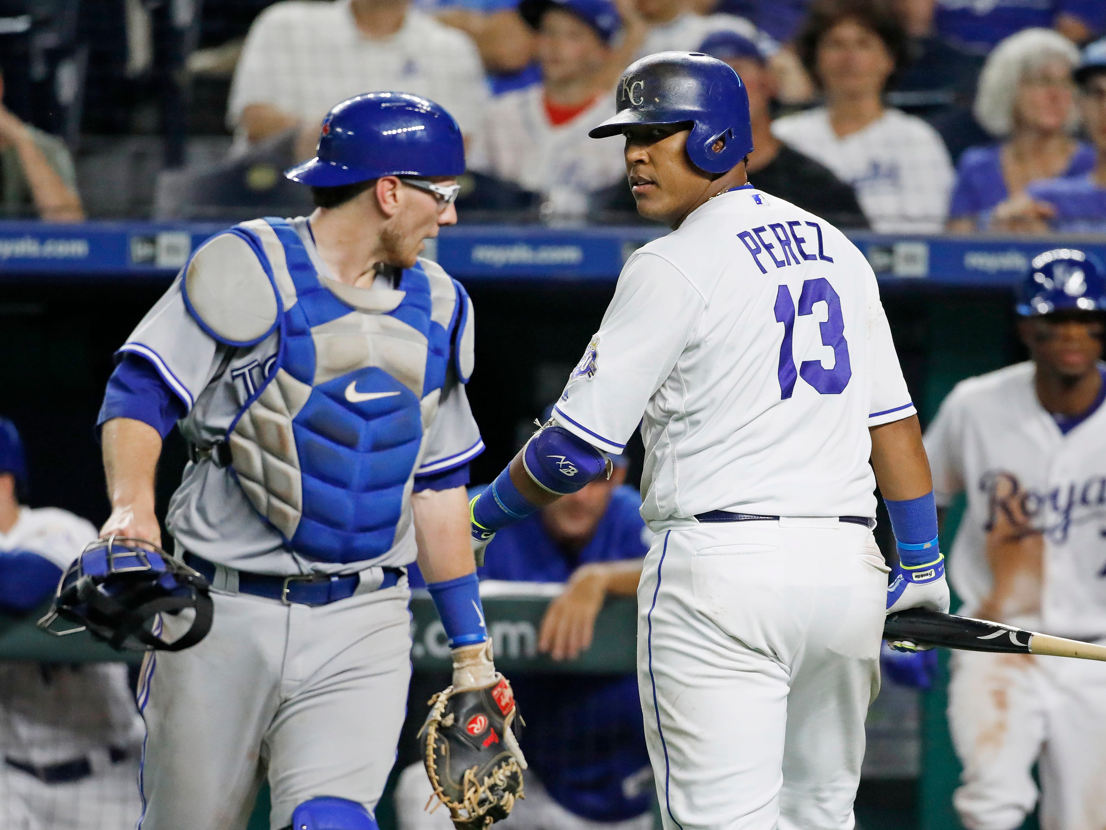 Kansas City Royals' Salvador Perez (13) looks back at Toronto Blue Jays catcher Danny Jansen (9) as they exchange words after Perez was out on a popup in the eighth inning of a baseball game at Kauffman Stadium in Kansas City, Mo., Monday, Aug. 13, 2018. (AP Photo/Colin E. Braley)