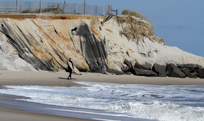 Jack Ryan, New Gretna, walks by eroded dunes at the southern end of Holgate Friday, October 12, 2018.