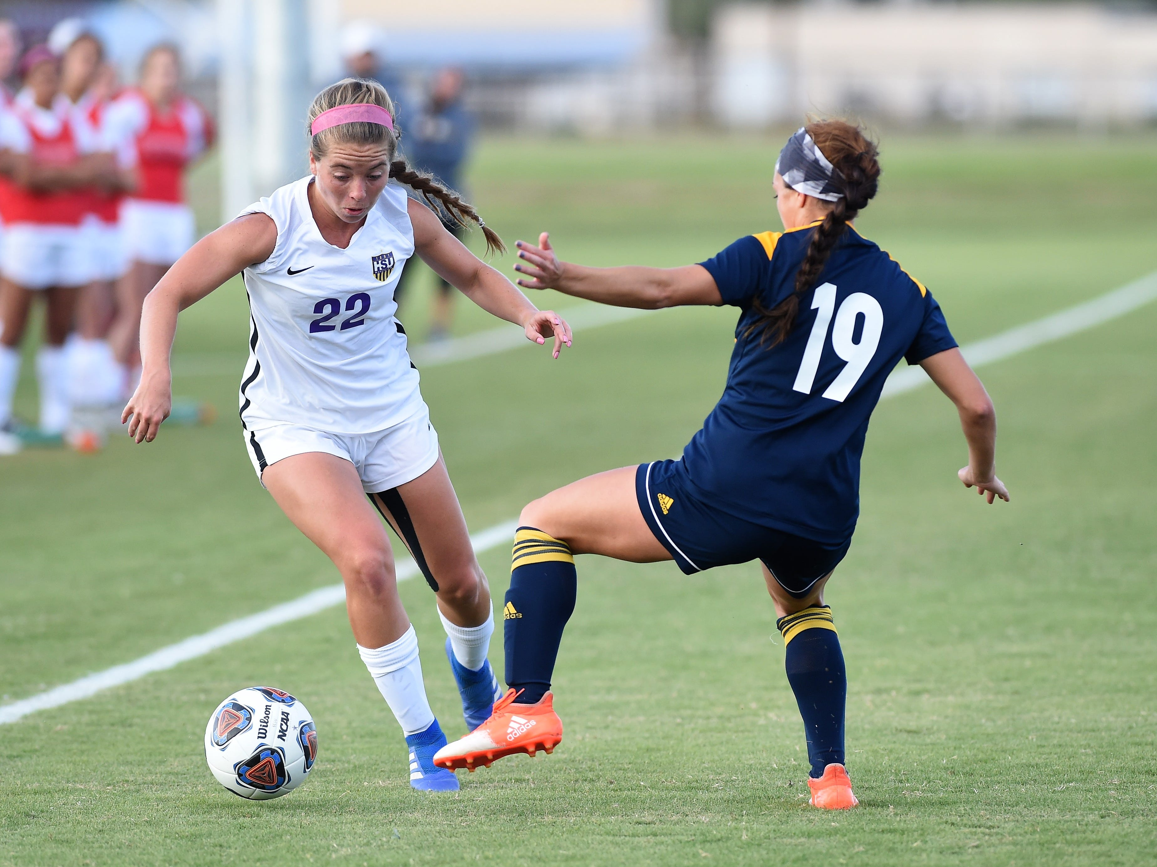 Hardin-Simmons defender Kendell Groom (22) makes a move past Howard Payne's Jayde Miyamoto (19) at the HSU Soccer Complex on Thursday, Oct. 11, 2018. The Cowgirls won 4-1.