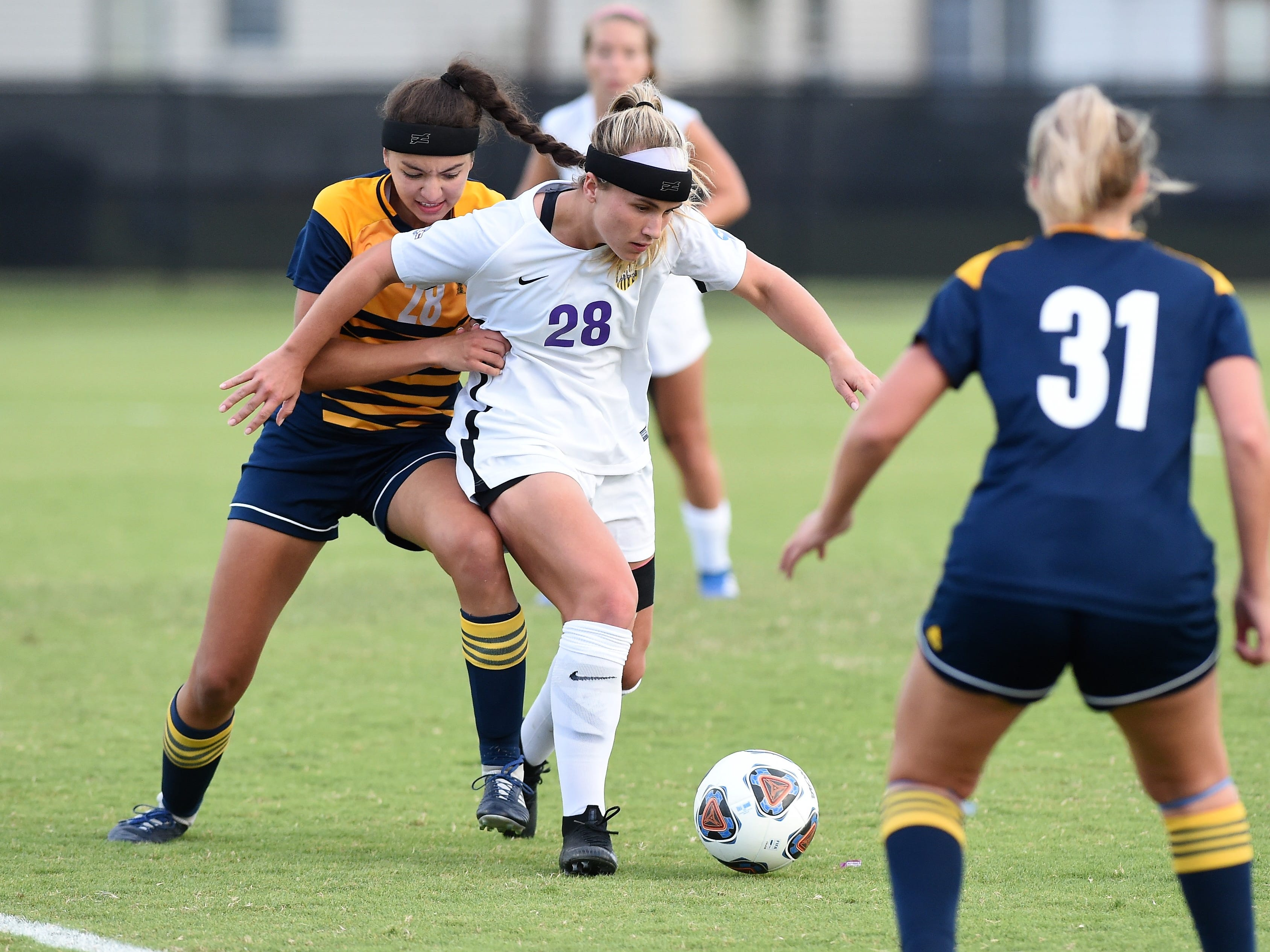 Hardin-Simmons midfielder Kenne Kessler (28) gets away from the grasp of Howard Payne's Leah Gordish (28) at the HSU Soccer Complex on Thursday, Oct. 11, 2018. The Cowgirls won 4-1.