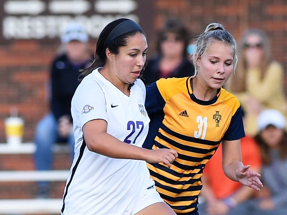 Hardin-Simons midfielder Elly Green (27) carries the ball past Howard Payne's Kate Van Wyk (31) at the HSU Soccer Complex on Thursday, Oct. 11, 2018. The Cowgirls won 4-1.