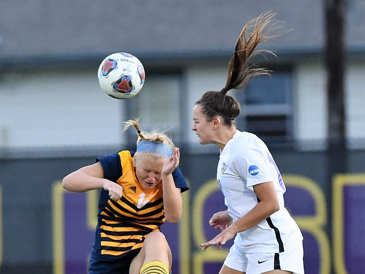 Hardin-Simmons midfielder Brenna Ebbinghaus (18) goes over Howard Payne's Chrissa Manning (14) for a header at the HSU Soccer Complex on Thursday, Oct. 11, 2018. The Cowgirls won 4-1.