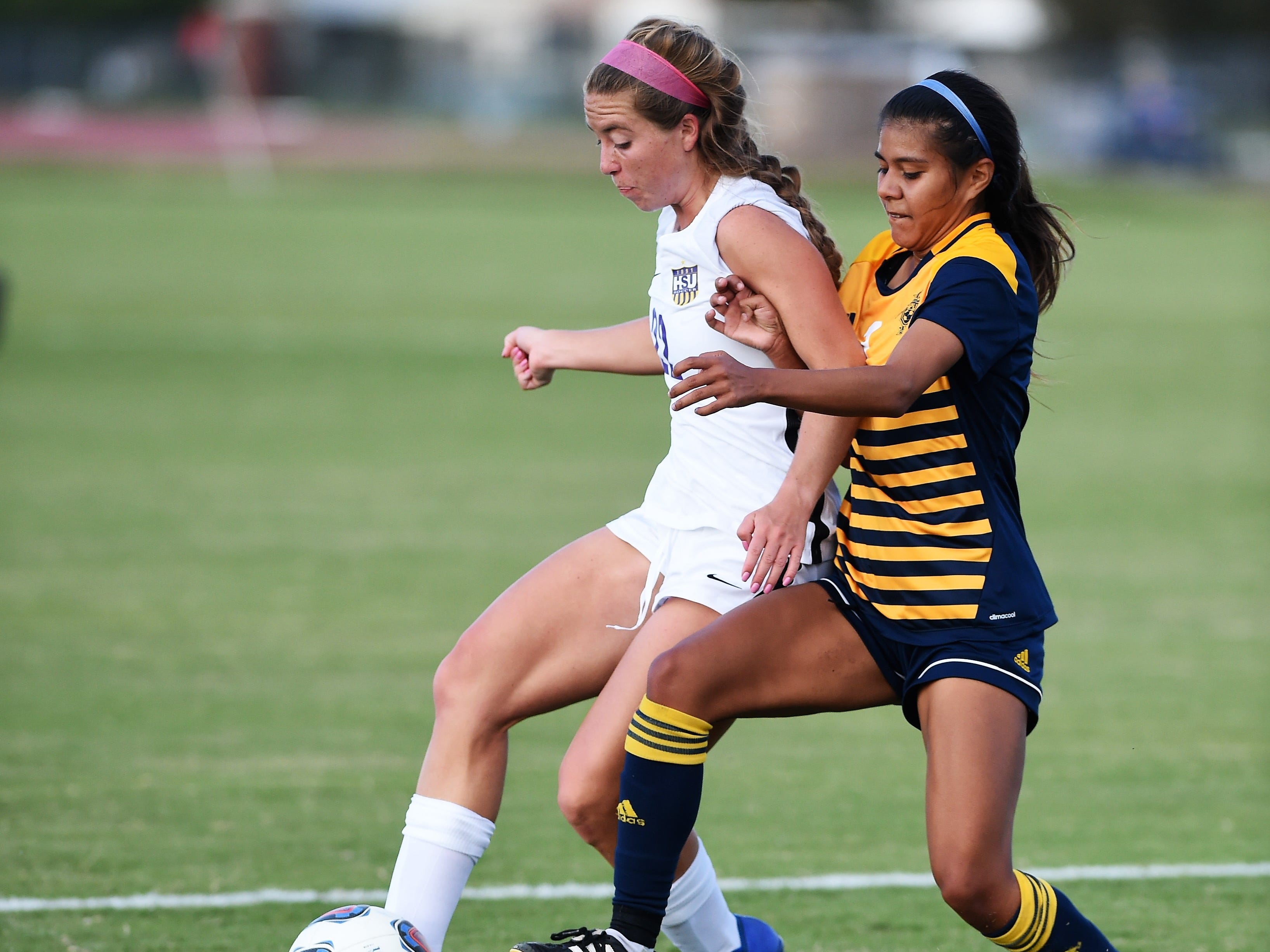 Hardin-Simmons defender Kendell Groom (22) holds off a Howard Payne defender at the ends of the box at the HSU soccer complex on Thursday, Oct. 11, 2018. The Cowgirls won 4-1.