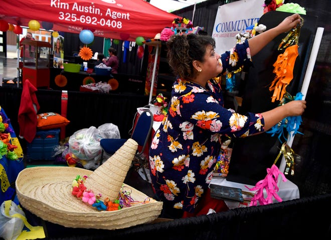 Linda Barfield hangs decorations at the Abilene Convention Center Friday. Barfield was setting up the Communities of Abilene Federal Credit Union booth for Business Mercado on Saturday.
