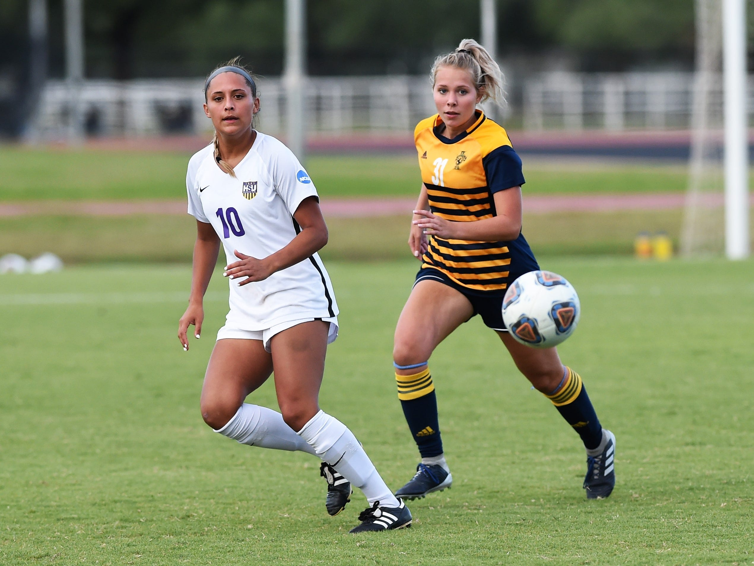 Hardin-Simmons forward Randie Dennison (10) turns to receive a pass in front of Howard Payne's Kate Van Wyk (31) at the HSU Soccer Complex on Thursday, Oct. 11, 2018. The Cowgirls won 4-1.