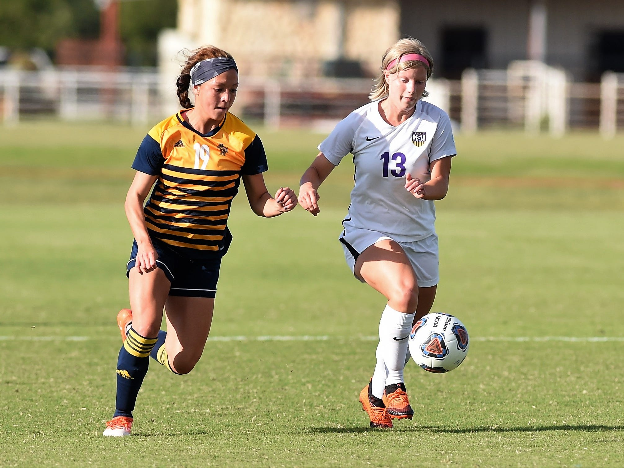 Hardin-Simmons midfielder Josey Meyer (13) holds off Howard Payne's Jayde Miyamoto (19) from the ball at the HSU Soccer Complex on Thursday, Oct. 11, 2018. The Cowgirls won 4-1.