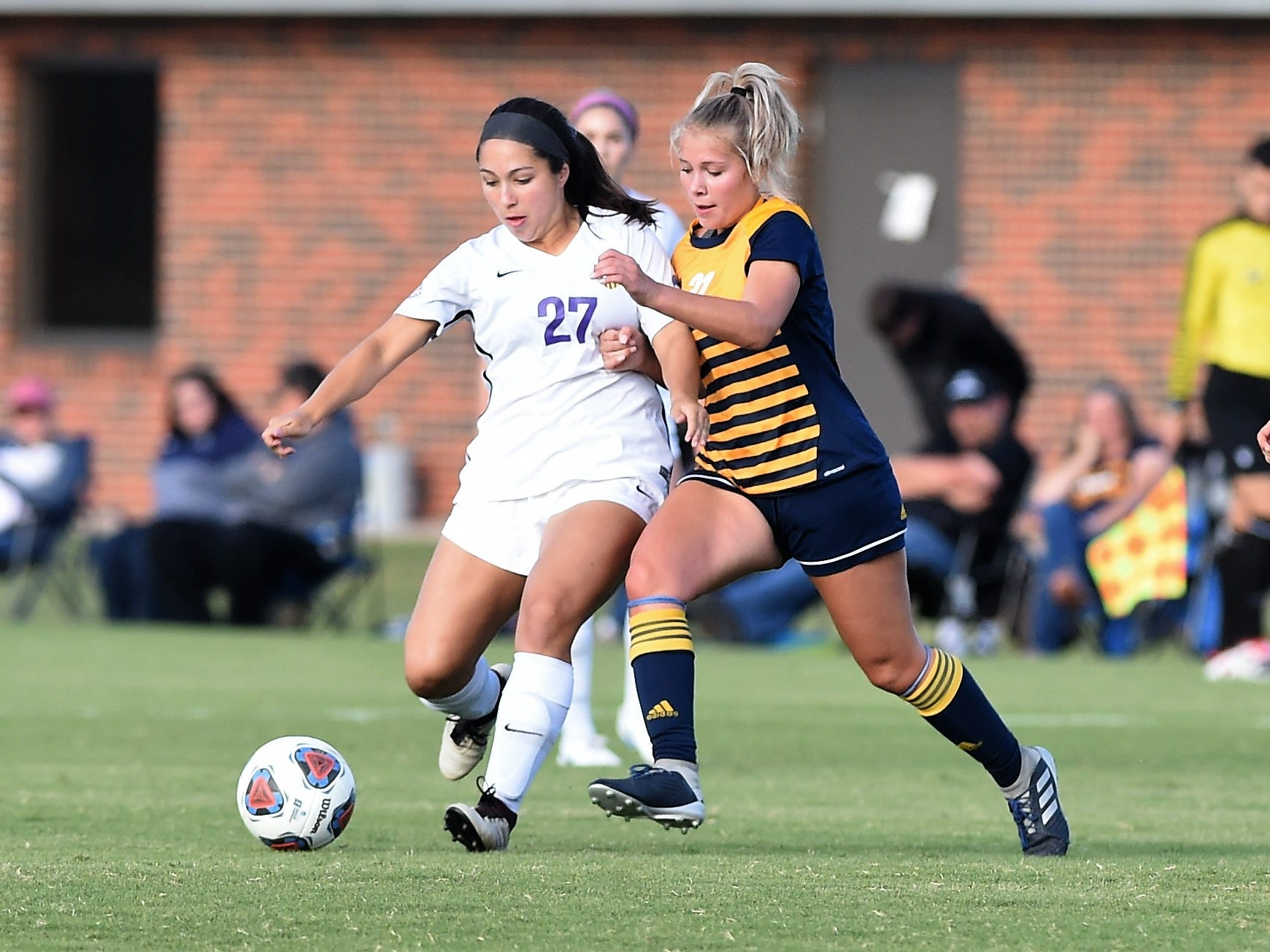 Hardin-Simmons midfielder Elly Green (27) passes with a Howard Payne defender on her back at the HSU Soccer Complex on Thursday, Oct. 11, 2018. The Cowgirls won 4-1.