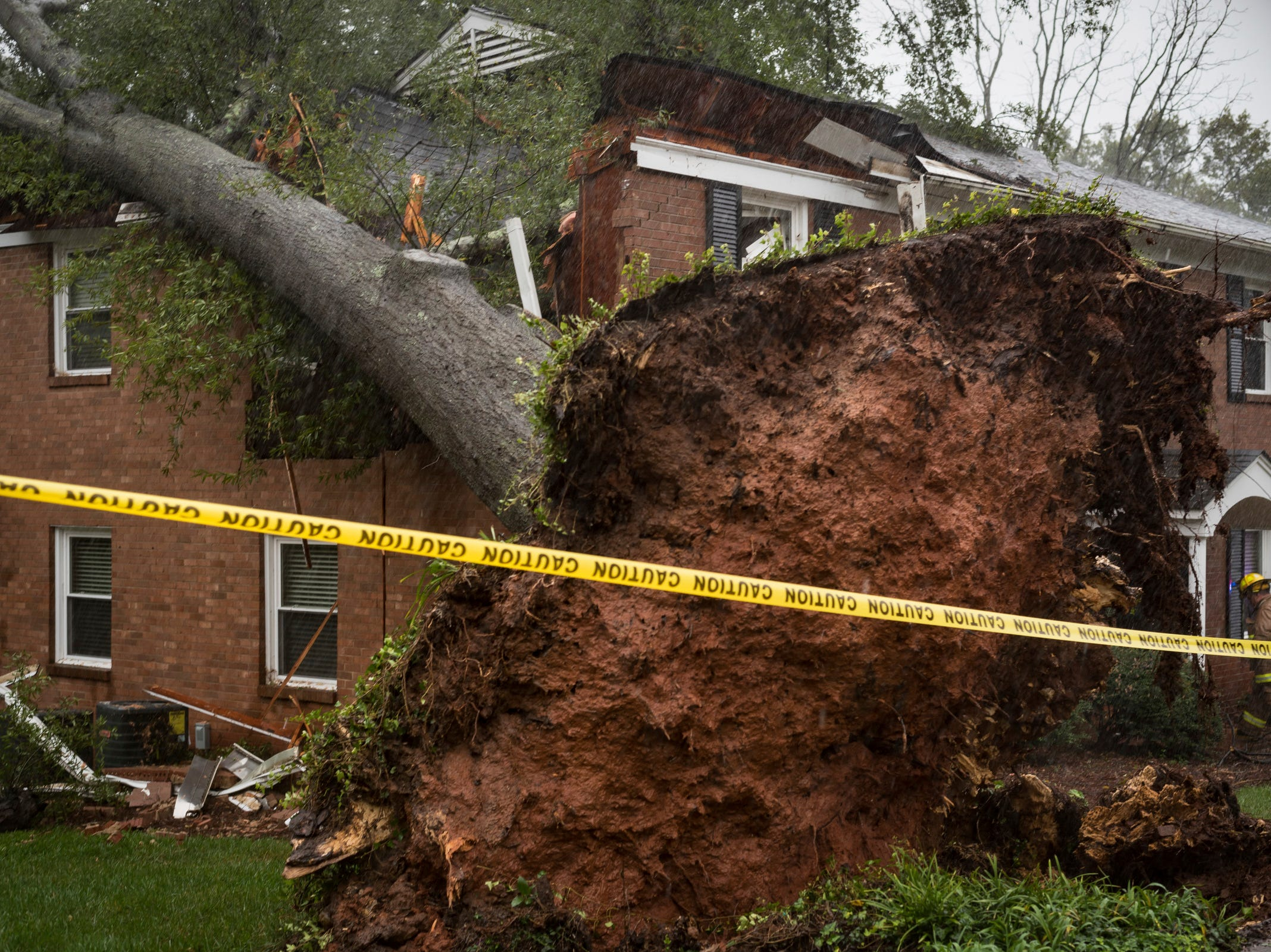 A Winston-Salem firefighter walks toward an apartment building which was struck by a toppled tree on Oct. 11, 2018, after the remnants of Hurricane Michael passed through Winston-Salem.
