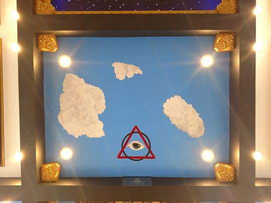 "An ""all-seeing eye"" , with clouds floating nearby painted by Carrie Jones on the ceiling of the Marshall Freemason's lodge."