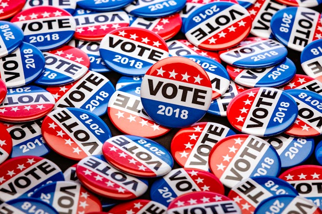 Stock photo of patriotic voting buttons for the mid term election, some with copy space on white or an American Flag.