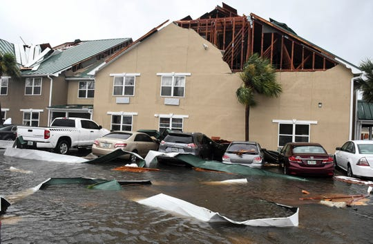 Parts of the roof of the Country Inn and Suites hotel in Panama City were deposited on cars in the parking lot and the lots next door. Mandatory Credit: Craig Bailey/FLORIDA TODAY via USA TODAY NETWORK