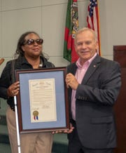 Camille Tate, president of the Space Coast Chapter of the National Federation of the Blind, receives a recognition from Brevard County Commissioner Curt Smith.