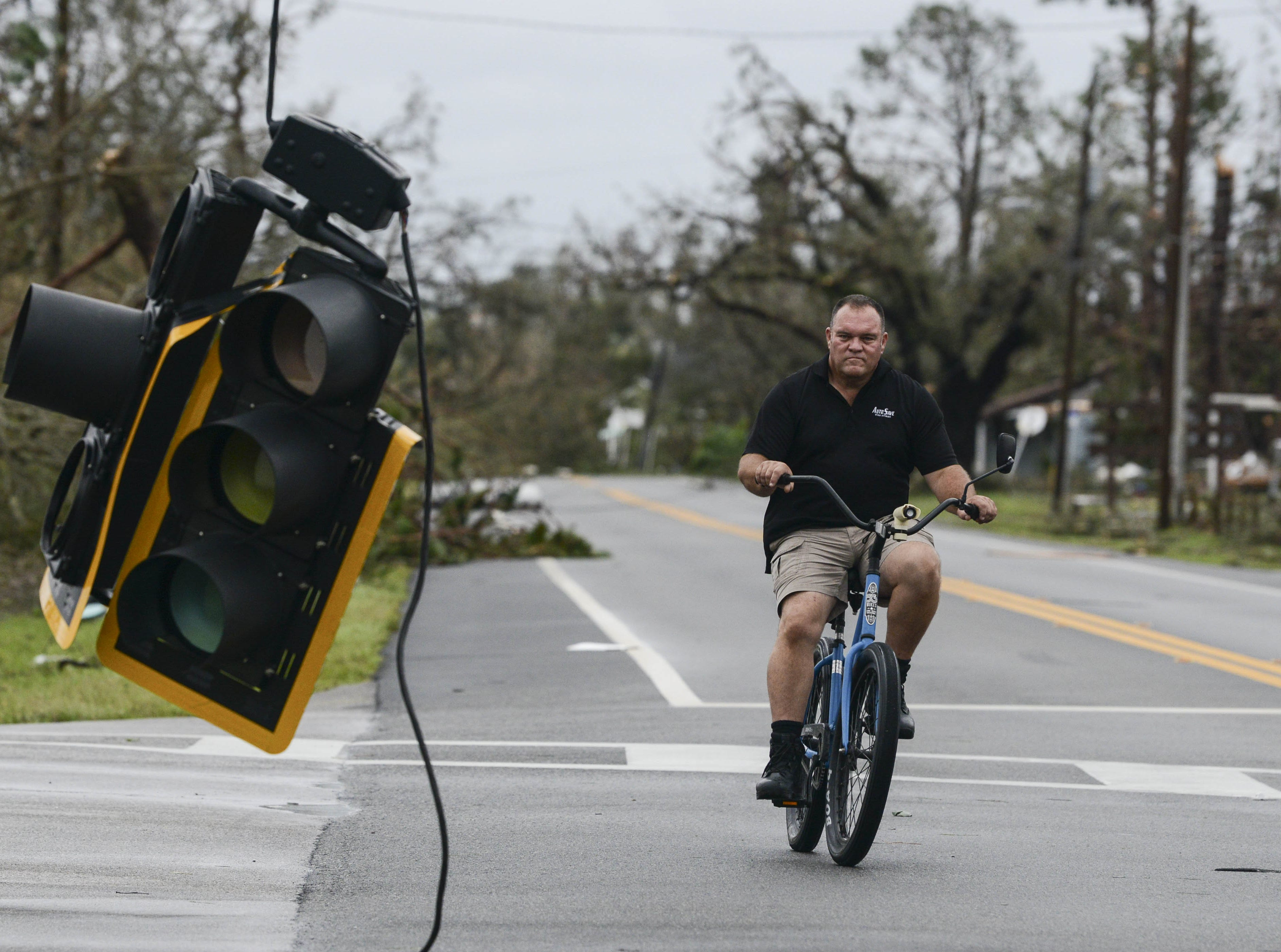 A bicyclist rides past a downed traffic light in Panama City, FL Wednesday after Hurricane Michael.