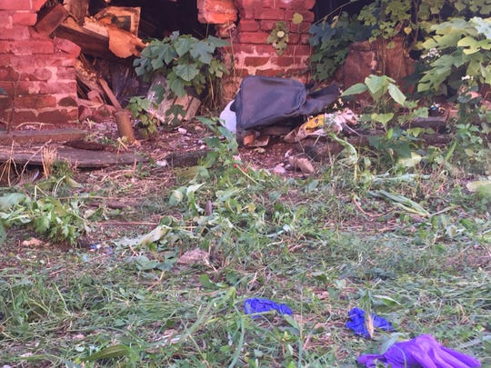 Latex gloves lie in a Camden alley where a child's body was found Thursday.