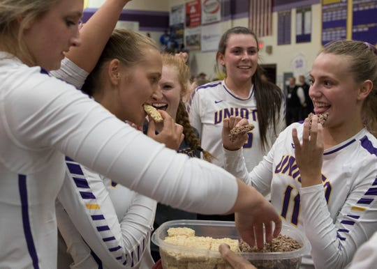 The Unioto girls' volleyball team enjoy rice crispy treats as they celebrate their win over Southeastern Thursday night at Unioto High School, making them SVC co-champions.
