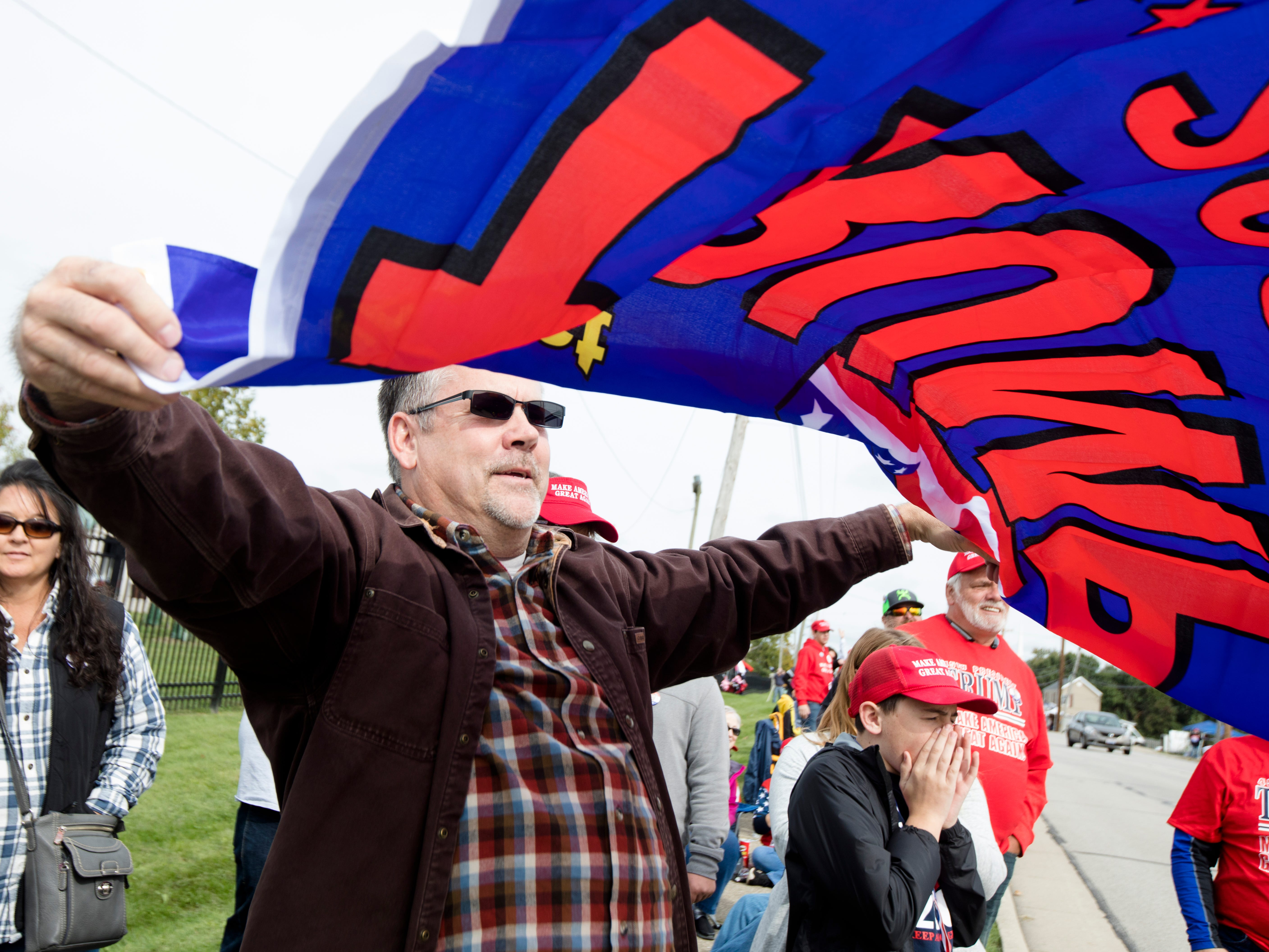 Chad Watson, of Hillsboro, Ohio, waives a flag in support of President Trump at traffic while waiting in line for President Donald J. Trump's Make America Great Again Rally in Lebanon, Ohio, on Friday, Oct. 12, 2018.