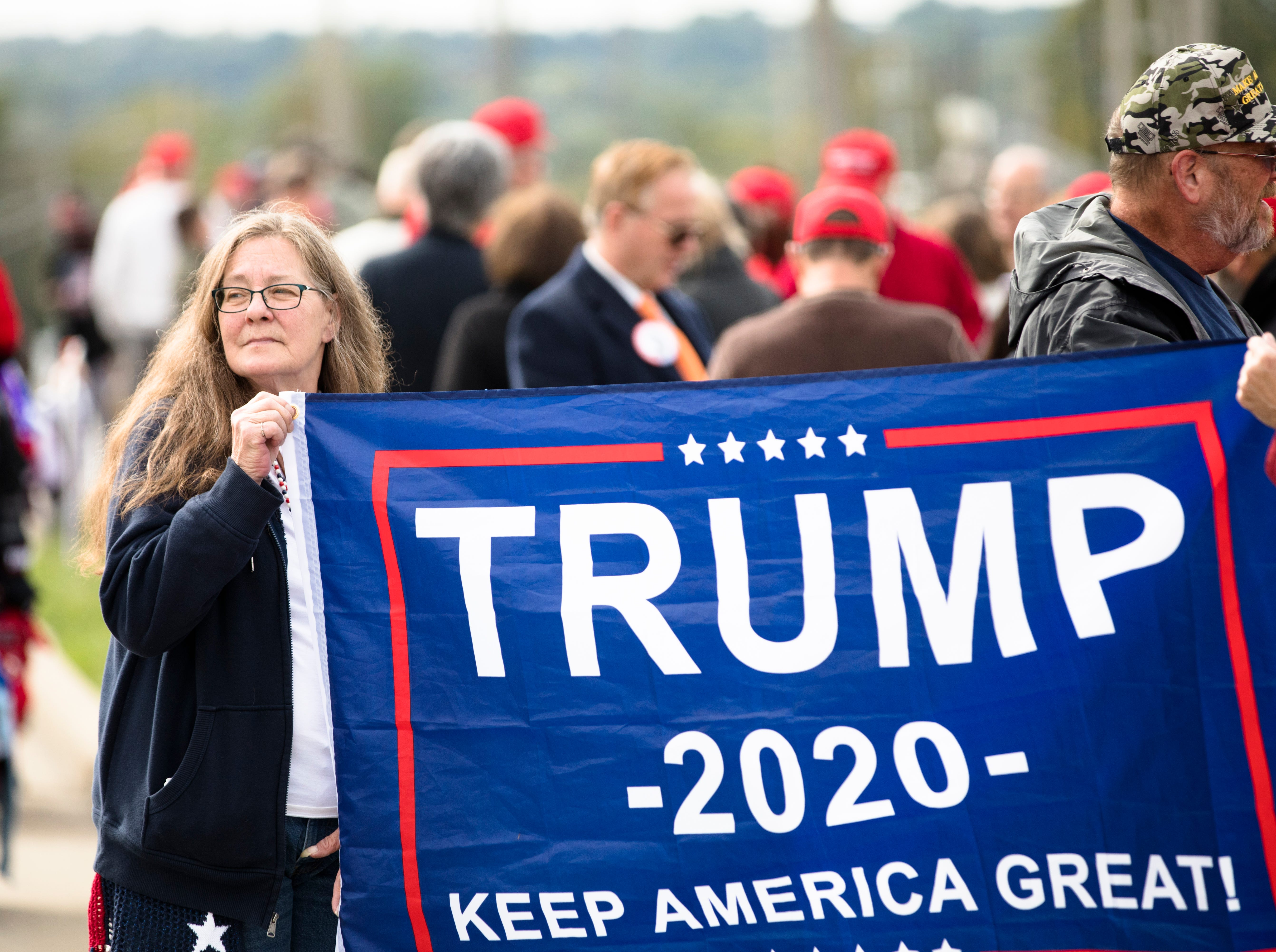 April Tate, of Green County, Ohio, holds a flag while waiting in line for President Donald J. Trump's Make America Great Again Rally in Lebanon, Ohio, on Friday, Oct. 12, 2018.