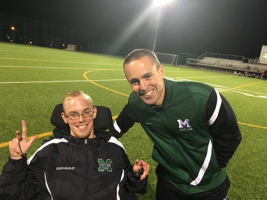 Mason girls soccer coach Andrew Schur smiles with chief assistant and No. 1 fan Bradley Tripp after their 1-0 victory over Fairfield to finish the GMC season unbeaten.