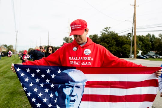 Lorenzo Esquivel holds a a flag while waiting in line for President Donald J. Trump's Make America Great Again Rally in Lebanon, Ohio, on Friday, Oct. 12, 2018.
