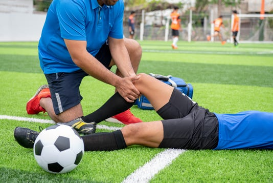 Footballer Wearing A Blue Shirt Black Pants Injured In The Lawn During The Race