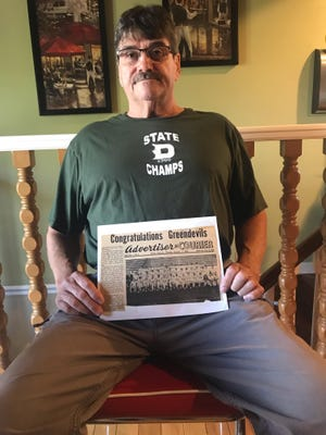 Allen Ramsey poses with a 1966 newspaper clipping congratulating Dayton High School on its Class A state championship.