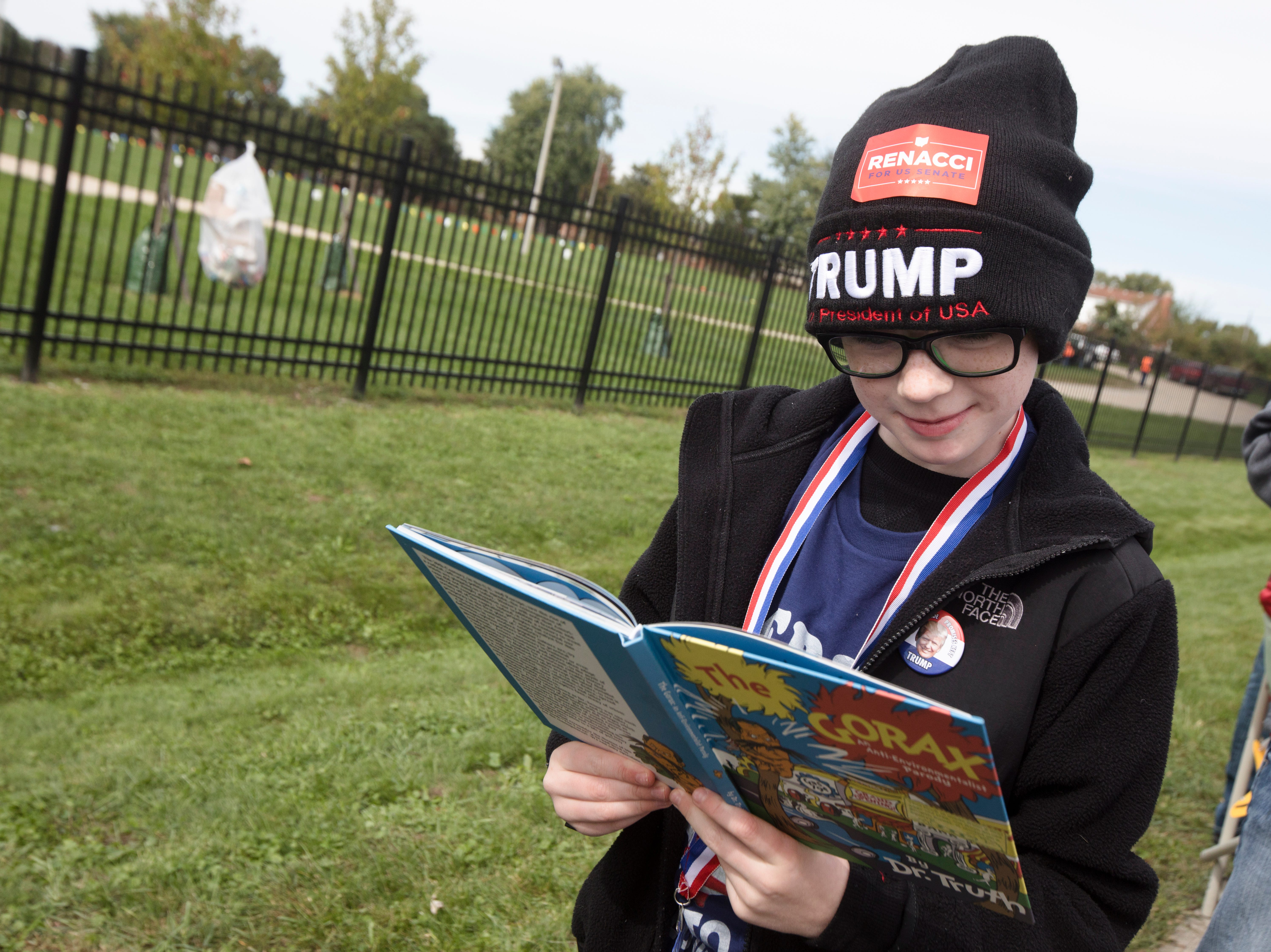"""Gabriel Allen, 9, reads """"The Gorax"""" while waiting in line for President Donald J. Trump's Make America Great Again Rally in Lebanon, Ohio, on Friday, Oct. 12, 2018."""