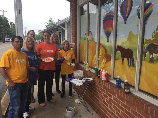 (Left to right) Gaurav Agrawal, Kathy Sliker, Nadya Hrycenko, Nancy Thompson, Kelsey McNeely and Ginny Pecca adorned United Way of Hunterdon County Volunteer Center windows with fall murals.