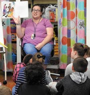"""Kirsten McPeck, third-grade teacher at Keene Elementary School, reads """"The Talking Cloth"""" to students. The social studies lesson was incorporated into an art project where students made their own Adinkra stamps."""