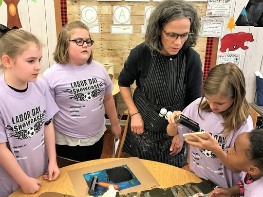 Anna Mitchell, Katie Parshall, Madelyn Jacob and Cheyenne Walls are instructed by Anne Cornell on inking stamps for an art project at Keene Elementary School.