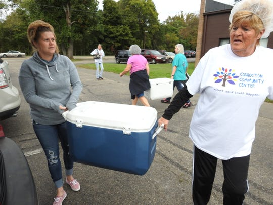 Jessie Jones and Bonnie Zimmer load a cooler into a vehicle for home meals delivery part of services offered through the Coshocton Senior Center. The home meal program and others will need to examined if the levy with addition fails on the November ballot.