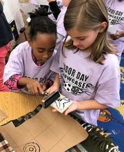 Cheyenne Walls and Madelyn Jacob ink a stamp for an art project connected to Adinkra symbols from Africa.