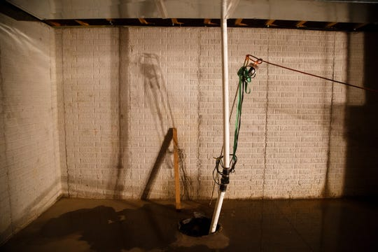 The sump pump hangs by a strap in the basement of what was supposed to be Krystal and Rusty Armstrong's dream home on Wednesday, Oct. 10, 2018, south of Indianola. They say contractor Dave Daughenbaugh has taken their money for work to be done but has walked off the job and left them with a shell of a building.